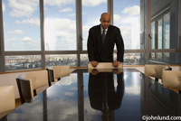 Picture of a single businessman standing at a conference table in a high rise office building. He has his hands on the back of one of the chairs placed around the table.